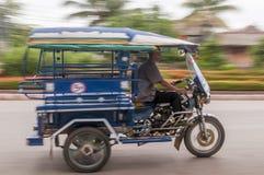 Panorera av en tuktuk som är rörande på gatorna av Luang Prabang, Laos royaltyfri fotografi