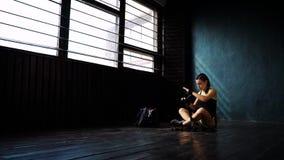 Panorera den färdiga kvinnan som slår in händer med, förbinda bandet som förbereder sig för att boxas utbildningsultrarapid stock video