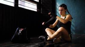 Panorera den färdiga kvinnan som slår in händer med, förbinda bandet som förbereder sig för att boxas utbildningsultrarapid lager videofilmer