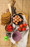 Panorera mycket av ägg, skivat bröd, ost, tomater, två koppar, knivar, rivjärnet på vitbok och kanfas Arkivbild