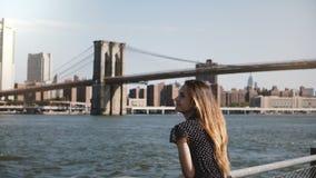 Panorera sikt av den lyckliga le europeiska kvinnan med flyghår som tycker om berömd New York horisont och sikt för Brooklyn bro arkivfilmer