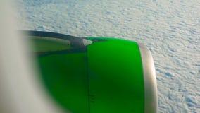 Panorera skottet av en grön flygplanmotor som flyger över moln lager videofilmer
