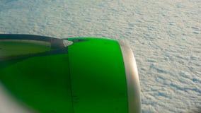 Panorera skottet av en grön flygplanmotor som flyger över moln arkivfilmer