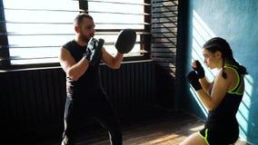 Panorera skottet av vit kvinnlig boxareutbildning för passform med boxninglagledaren på idrottshallen arkivfilmer
