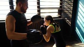 Panorera skottet av vit kvinnlig boxareutbildning för passform med boxninglagledaren på idrottshallen lager videofilmer