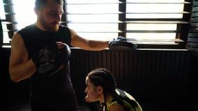 Panorera skottet av vit kvinnlig boxareutbildning för passform med boxninglagledaren på idrottshallen stock video