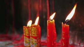 Panorera skottet på brinnande stearinljus på den buddistiska kinesiska templet stock video