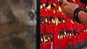 Panorera skottet på brinnande stearinljus för folk arkivfilmer