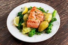 Panorera stekte Salmon Served med potatisar och tenderstembroccoli Royaltyfri Foto