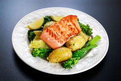 Panorera stekte Salmon Served med potatisar och tenderstembroccoli Royaltyfria Bilder