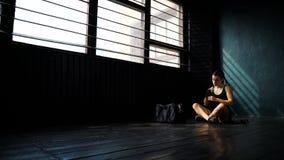 Panorera ungt härligt kvinnasammanträde på golv och inpackning av händer med svarta boxningsjalar i klubba stock video