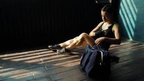 Panorera ungt härligt kvinnasammanträde på golv och inpackning av händer med svarta boxningsjalar i klubba lager videofilmer