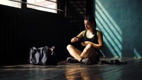 Panorera ungt härligt kvinnasammanträde på golv och inpackning av händer med svarta boxningsjalar i klubba arkivfilmer
