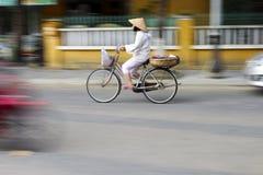 Panorerat skott som visar en kvinna som cyklar i Vietnam arkivfoto