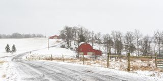 Panorma of winter scene of rural farm in Appalachia. Panoramic winter scene of a snow-covered gravel lane leading past a farm with red barns in rural Appalachia stock images
