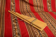 Panpipes from South America sitting against a red textile Stock Photo
