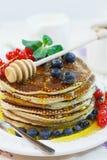 Panqueca com mel e bagas Fotografia de Stock Royalty Free