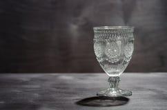 Panqueca de cristal vazia com um teste padrão, em um fundo de madeira escuro Imagens de Stock Royalty Free