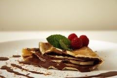 Panqueca do chocolate com framboesas e folhas da hortelã imagens de stock royalty free