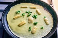 A panqueca do milho é cozinhada em uma frigideira com queijo e as cebolas verdes foto de stock royalty free