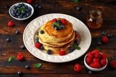 Panquecas americanas caseiros com mirtilo, as framboesas e mel frescos Estilo rústico do café da manhã saudável da manhã fotografia de stock royalty free