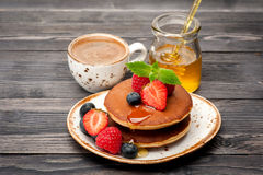 Panquecas caseiros com mel, café e bagas Imagens de Stock Royalty Free