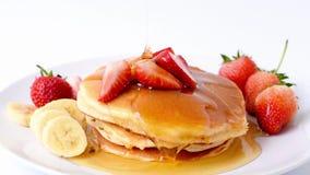 Panquecas caseiros com morangos e banana e mel frescos da fatia na placa branca, café da manhã saudável filme