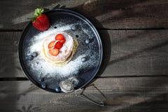 Panquecas caseiros com morangos, mirtilos e a??car pulverizado Pequeno almo?o doce fotografia de stock royalty free