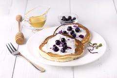 Panquecas cobertas com mel e mirtilos do queijo creme das panquecas saborosos caseiros brancas do fundo da placa no café da manhã Foto de Stock