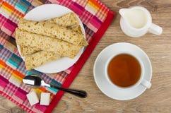 Panquecas com enchido, açúcar, colher de chá no guardanapo, chá, leite imagens de stock