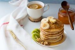 Panquecas com frutos, doce e tampão do chá em uma tabela branca imagens de stock royalty free