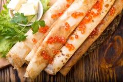 Panquecas com manteiga e caviar em uma textura de madeira Imagens de Stock Royalty Free