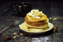 Panquecas com manteiga e mel em um fundo preto Imagens de Stock Royalty Free