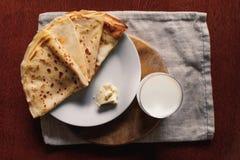 Panquecas com manteiga e vidro do leite na opinião superior do close up de madeira da tabela Imagem de Stock