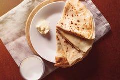 Panquecas com manteiga e vidro do leite na tabela de madeira closeup Vista superior Fotografia de Stock