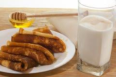 Panquecas com mel e um vidro do leite fresco Imagem de Stock Royalty Free