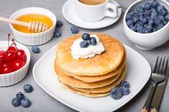 Panquecas com mirtilos, cerejas, creme de leite, mel e café Fotografia de Stock