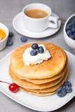 Panquecas com mirtilos, cerejas, creme de leite, mel e café Fotos de Stock Royalty Free