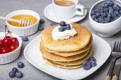Panquecas com mirtilos, cerejas, creme de leite, mel e coffe Foto de Stock