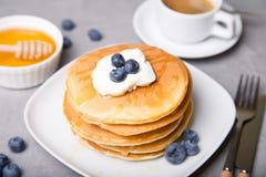 Panquecas com mirtilos, creme de leite, mel e café Imagens de Stock