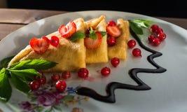 Panquecas com morangos e corintos do mel em uma placa Fotos de Stock Royalty Free