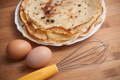 Panquecas com ovos e batedor de ovos na placa de corte de madeira Imagem de Stock