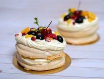 Panquecas com vários frutos e um creme delicado em um fundo branco de madeira Imagem de Stock