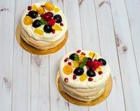 Panquecas com vários frutos e um creme delicado em um fundo branco de madeira Fotografia de Stock