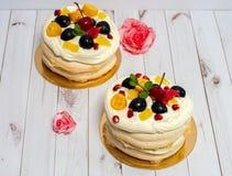 Panquecas com vários frutos e um creme delicado em um fundo branco de madeira A tabela é decorada com as duas rosas cor-de-rosa Imagem de Stock