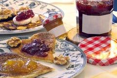 Panquecas coração-dadas forma deliciosas com doce da morango e do pêssego e algumas porcas foto de stock