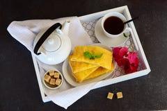 Panquecas de queijo com chá em uma bandeja de madeira Foto de Stock