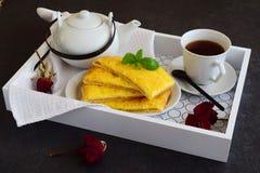 Panquecas de queijo com chá em uma bandeja de madeira Fotografia de Stock Royalty Free