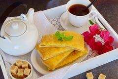 Panquecas de queijo com chá em uma bandeja de madeira Foto de Stock Royalty Free