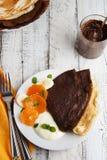 Panquecas delicadas finas do chocolate, roladas com frutos e creme Fundo de madeira branco Pequeno almoço doce fotos de stock